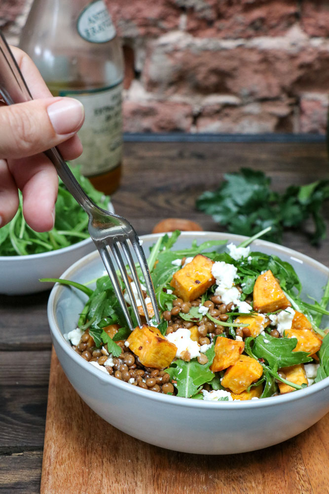 Een lekkere lunch salade met zoete aardappel, linzen en feta maak je makkelijk zelf. Door de aardappels te roosteren worden ze heerlijk zoet. De feta combineert dan perfect! #herfstrecepten #zoeteaardappel