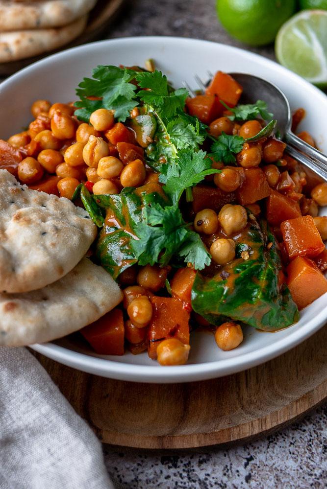 Herfstig comfort food zet je makkelijk op tafel met deze vergetarische zoete aardappel curry met kikkererwten en spinazie. Serveer met rijst of naanbrood. #curry #zoeteaardappel #vegetarisch
